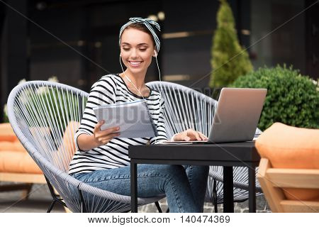 Pleasant work. Cheerful charming content woman sitting at the table and listening to music while using laptop
