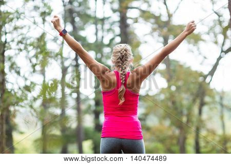 Excited woman standing with arms outstretched in forest