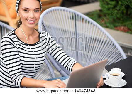 Improve your mood. Delighted positive charming woman sitting in the cafe and listening to music while using laptop
