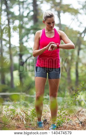 Beautiful woman checking time on wristwatch in forest