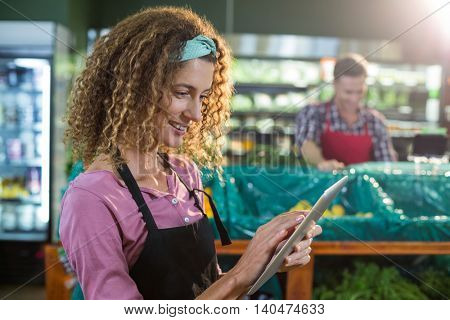 Smiling female staff using digital tablet in organic section of supermarket