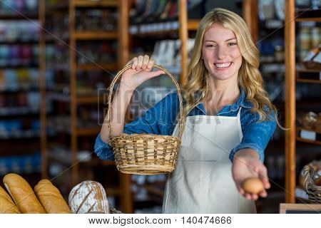 Portrait of smiling female staff holding basket and egg in super market