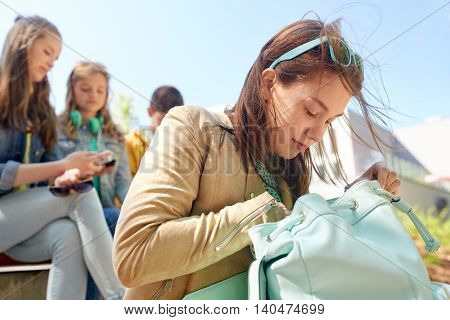 education, high school and people concept - happy teenage student girl looking for something in her backpack outdoors