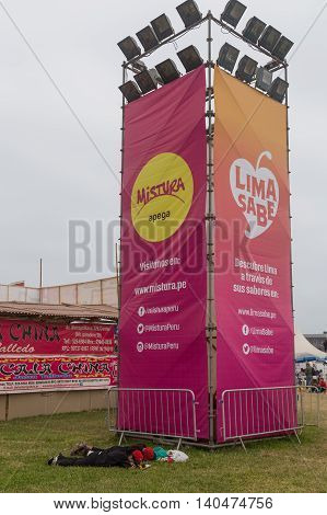 Lima, Peru - September 11, 2015: People sleeping in front of a Mistura Festival sign post