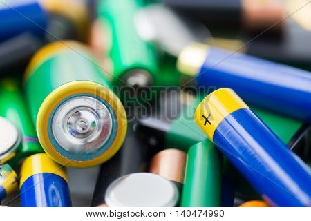 recycling, energy, power, environment and ecology concept - close up of alkaline batteries heap