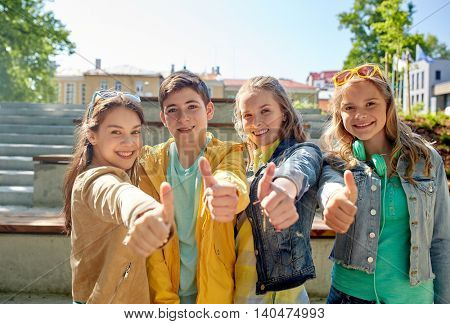 education, high school, friendship, gesture and people concept - group of happy teenage students or friends showing thumbs up outdoors