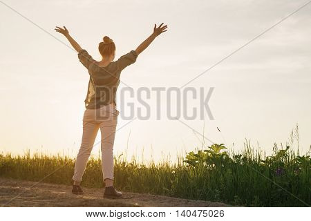 female teen girl stand feel freedom with arms stretched to the sky copy space for your info, sunset light