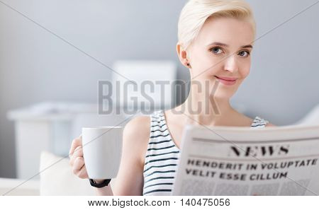 Everything is illuminated. Smiling pleasant middle-aged woman looking at the camera while holding a newspaper and a cup of coffee