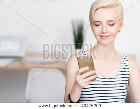 I have a new message. Pleased young woman sitting and looking at her mobile phone