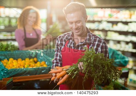 Smiling staff holding bunch of carrots in organic section of supermarket