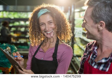 Smiling staffs writing on clipboard in organic section of supermarket