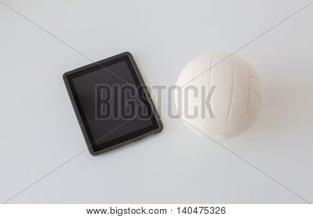 sport, fitness, game, sports equipment and technology concept - close up of volleyball ball and tablet pc computer with black blank screen on white background