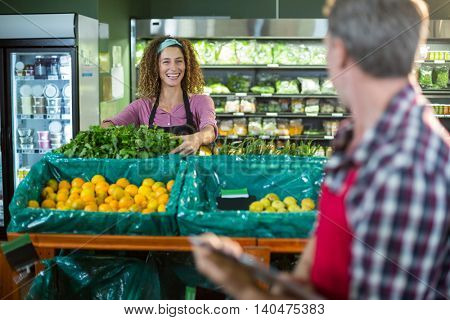 Smiling staffs interacting with each other in organic section of supermarket