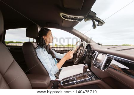 leisure, road trip, technology, travel and people concept - happy woman driving car with smarhphone