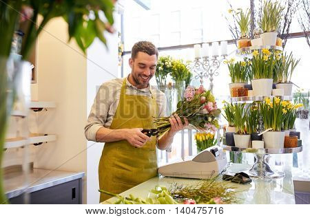 people, business, sale and floristry concept - happy smiling florist man making bunch and cropping stems by scissors at flower shop