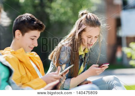 technology, internet and people concept - happy teenage boy with tablet pc computer and girl with smartphone outdoors