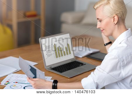 I have to work. Woman working on her laptop while sitting at the table and looking at the paper with a diagram
