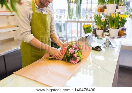 people, shopping, sale, floristry and consumerism concept - close up of happy florist man wrapping flowers in paper at flower shop
