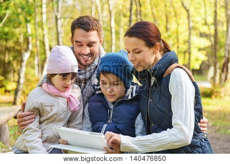 camping, travel, tourism, hike and people concept - happy family with tablet pc computer at camp in woods