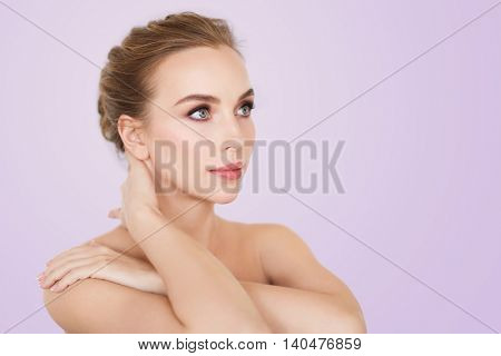 beauty, people and bodycare concept -beautiful young woman face and hands over violet background