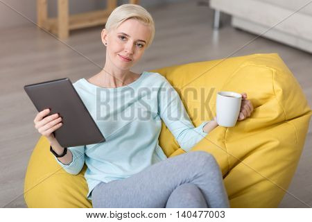 Good finish of a working day. Tired smiling woman looking at the camera while sitting on the bean bag and holding a cup of tea and a tablet in her hands