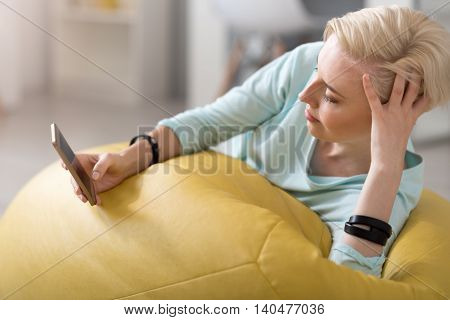 I need a rest. Delighted woman lying on the bean bag and using her smartphone at home