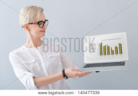 Have a look. Clever woman with glasses holding a laptop with diagram on the screen and looking at it