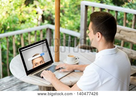 business, internet, information, people and technology concept - close up of businessman typing on laptop with search browser bar on screen outdoors on summer terrace and drinking coffee