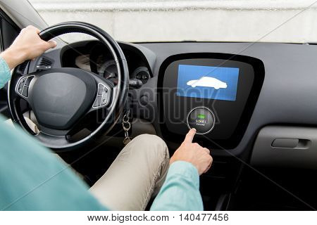 transport, road trip, technology and people concept - close up of man driving car and pushing start engine button on board computer