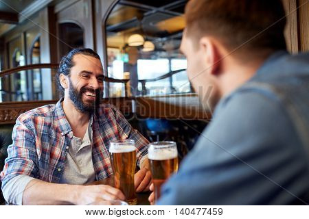 people, men, leisure, friendship and communication concept - happy male friends drinking draft beer at bar or pub