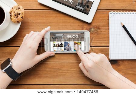 technology, business, communication, people and advertisement concept - close up of woman with blank smartphone screen and coffee cup on wooden table