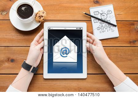communication, business, technology and people concept - close up of woman with e-mail icon on tablet pc computer screen, notebook and coffee on wooden table