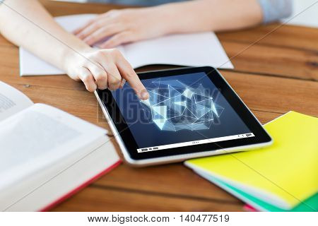 education, technology, network and internet concept - close up of student woman with low poly shape on tablet pc computer screen and notebook at home