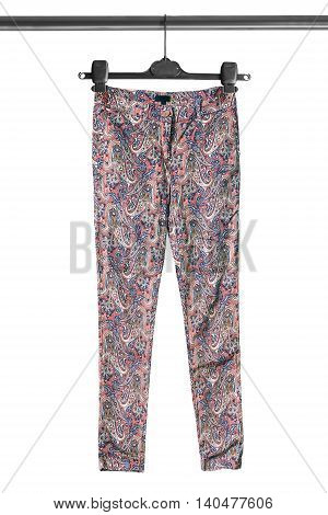 Colorful silk pants on clothes rack isolated over white