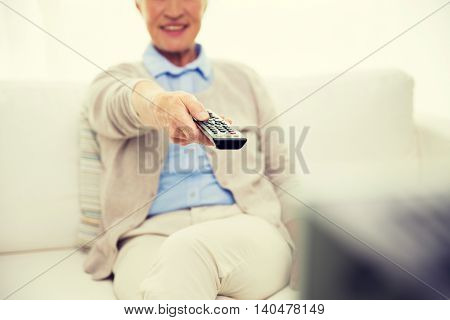 family, technology, television, age and people concept - close up of happy senior woman watching tv at home