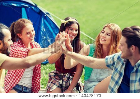 travel, tourism, hike and people concept - group of happy friends with tent making high five at camping