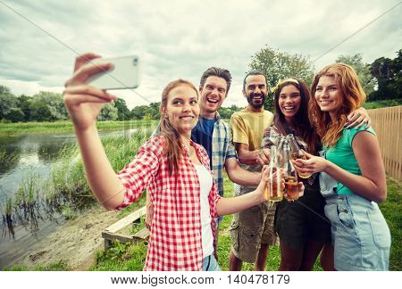 camping, travel, tourism, hike and people concept - happy friends with glass bottles drinking cider or beer and taking selfie by smartphone at camping