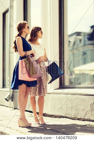 sale, consumerism and people concept - happy young women with shopping bags looking at shop window in city