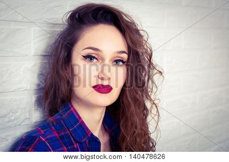 Portrait of Glamour Hipster Girl on White Brick Wall Background. Trendy Casual Fashion Makeup. Toned Photo with Copy Space.