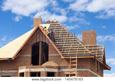 House under construction. Workesr installing fibreboard on the roof