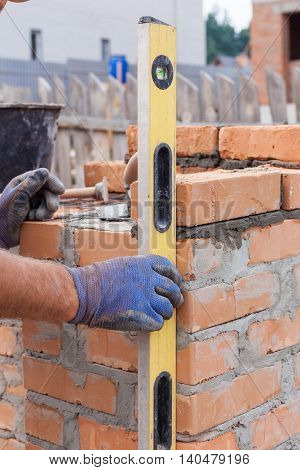 Construction mason worker measuring with professional level the bricks on walls