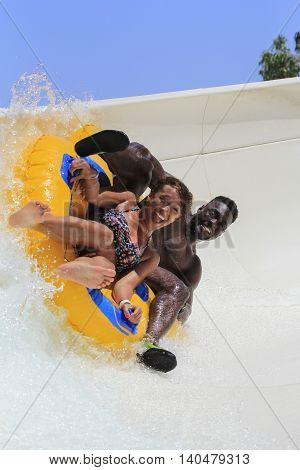 Rhodes Greece-July 2 2016:Young black couple drive with tube on the rafting slide in the Water park.Rafting slide is one of many popular game for adults and children in park.Water Water Park is located in Faliraki on the island of Rhodes in Greece and one