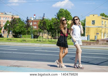 Two cheerful girls, summer street outdoors