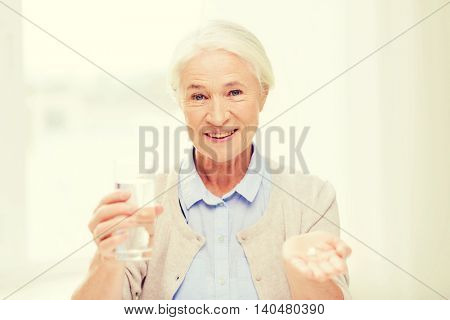 age, medicine, health care and people concept - happy senior woman with pills and glass of water at home