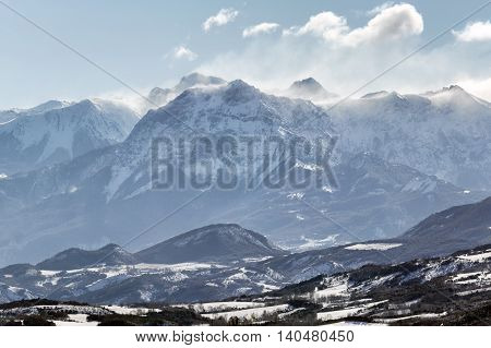Winter morning view of the Grand Morgon peak with wind blowing fresh snow. Hautes Alpes, Southern French Alps, France