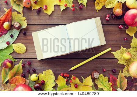 nature, season, inspiration and memories concept - close up of empty note book or album with pencil in frame of autumn leaves, fruits and berries on wooden table