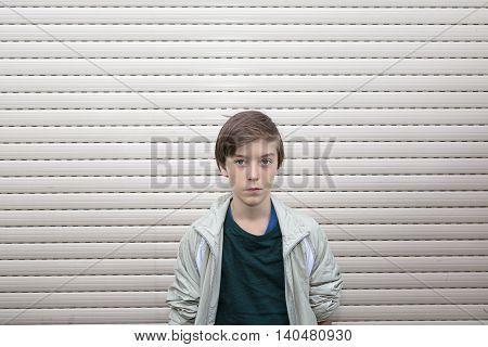 Portrait Of A Boy With Gray Roller Shutter In Background