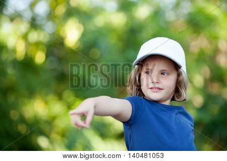 Little cute girl with a cap in the park indicating the direction