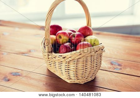 gardening, season, autumn and fruits concept - close up of wicker basket with ripe red apples on wooden table
