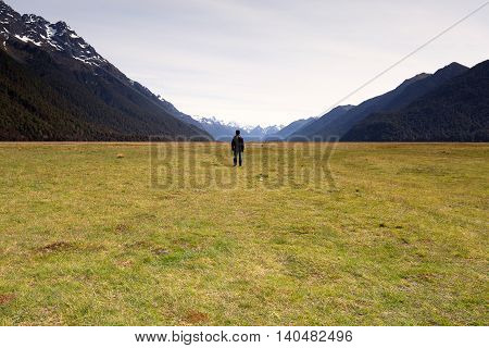 A man standing and facing a vast empty landscape.